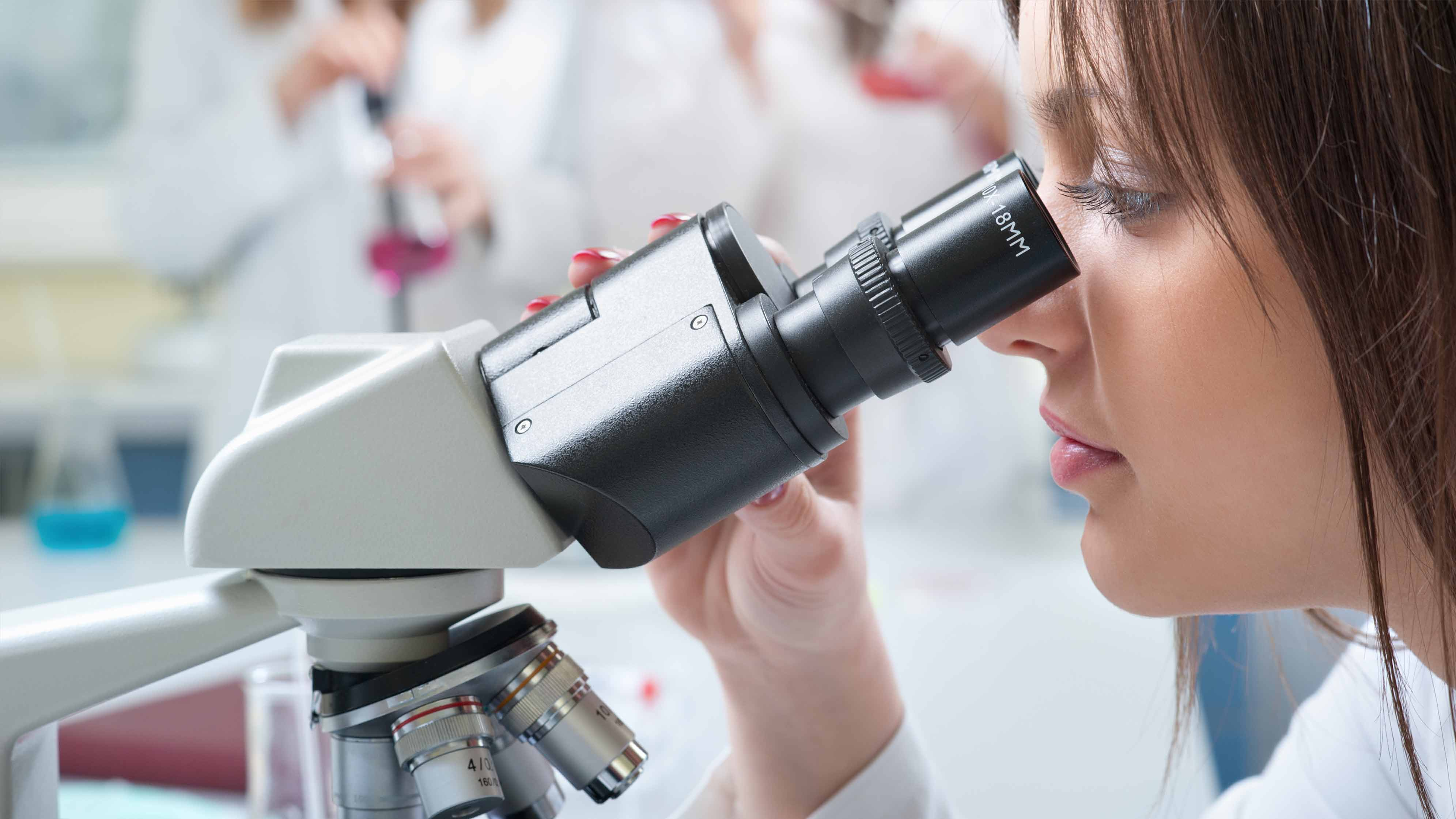 Mandl School Medical Degree student looking into microscope